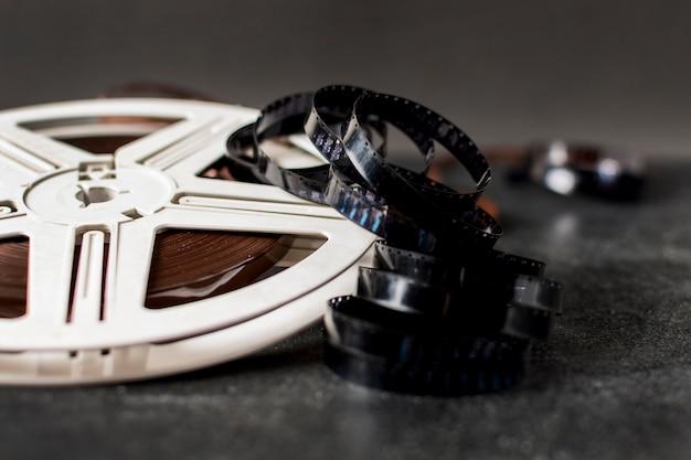 Bobina di pellicola e strisce di pellicola su sfondo scuro