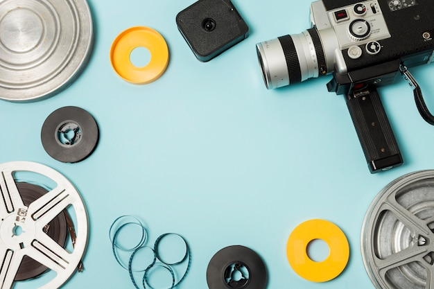 Bobina; strisce di pellicola e videocamera su sfondo blu con copia spazio per la scrittura del testo