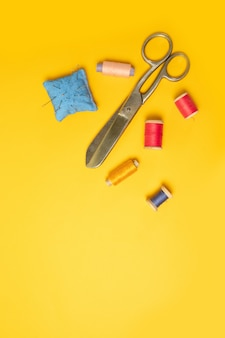 Bobine di fili colorati multi rosa, nastro di misurazione, aghi per macchine da cucire su uno sfondo. accessori per cucire per cucito, cucito.