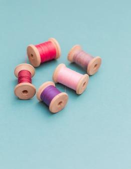 Bobine di fili multicolori su un ricamo blu cucito ricamo a mano vista dall'alto concetto piatto disteso diverse variabili diverse