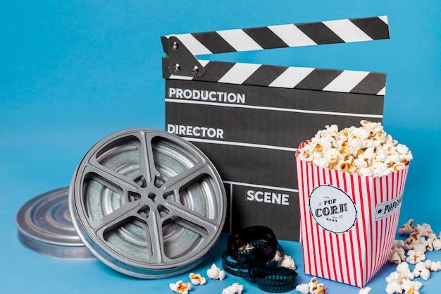 Bobine di film; strisce di pellicola e ciak con scatola di popcorn su sfondo blu
