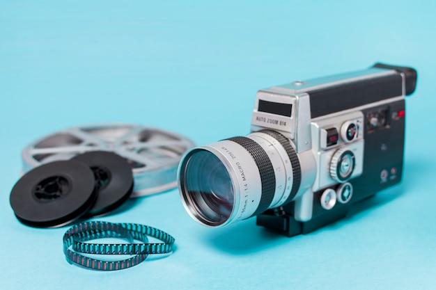 Bobine di film; strisce di pellicola e videocamera vintage su sfondo blu