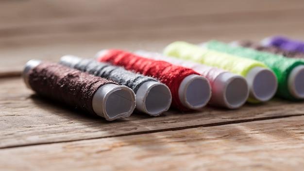 Bobine di filo multicolore su superficie di legno
