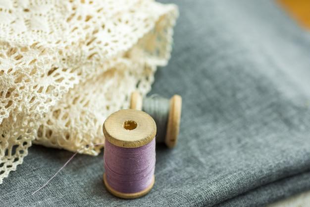 Bobine di legno vintage con fili lilla e grigi su tessuto di lana piegato, pizzo di cotone