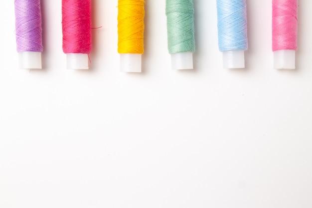 Bobine multicolori del filo su bianco. vista piana, vista dall'alto