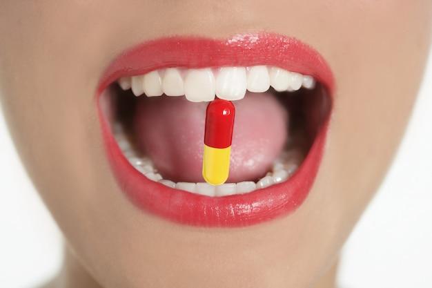 Bocca della donna di bellezza con la pillola della medicina