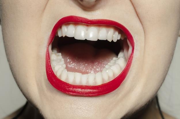 Bocca femminile del primo piano con trucco rosso brillante delle labbra di lucentezza.