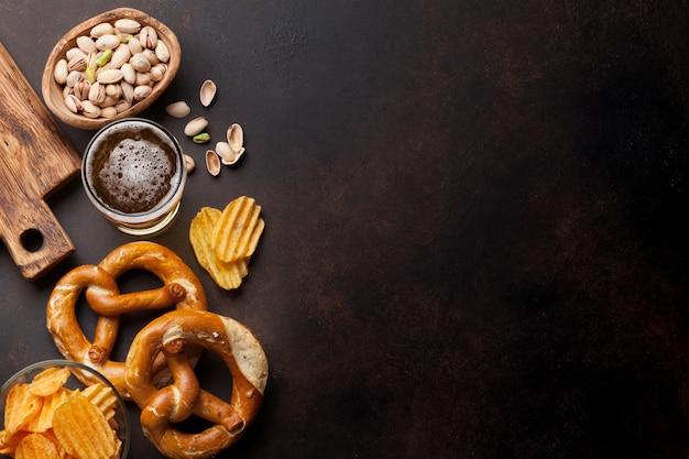 Boccale di birra chiara e snack sul tavolo di pietra