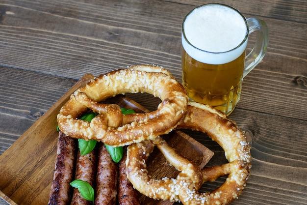 Boccale di birra chiara, salatini e salsicce fritte su legno