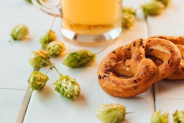 Boccale di birra, coni di luppolo e salatini su un tavolo di legno bianco.