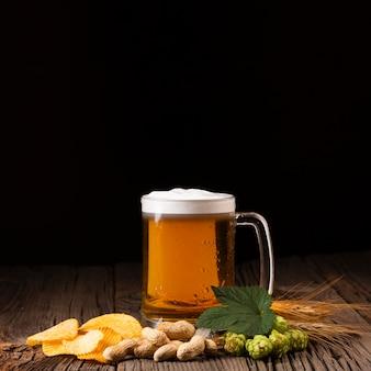Boccale di birra del primo piano con gli spuntini