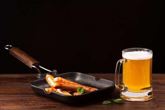 Boccale di birra del primo piano con le salsiccie
