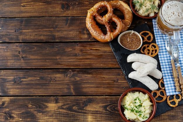 Boccale di birra, salatini e salsicce sul fondo della tavola in legno in vista dall'alto