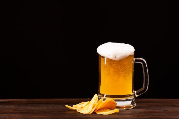 Boccale di birra vista frontale con patatine
