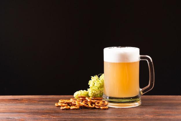 Boccale di birra vista frontale con salatini