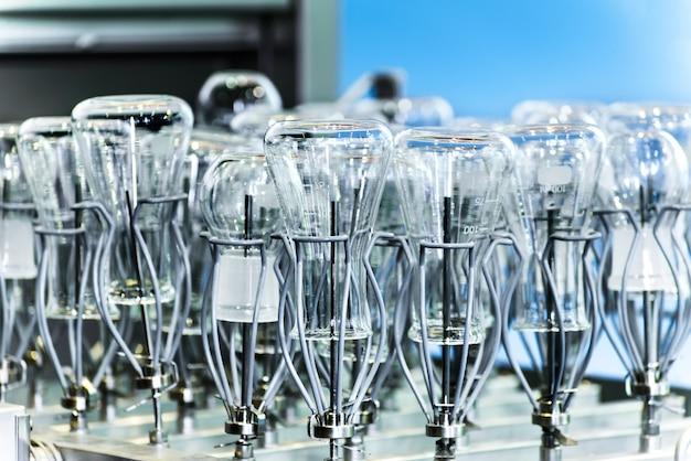 Boccette e provette inserite nella lavastoviglie industriale del vassoio.