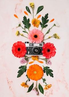Boccioli di fiori con fotocamera sul tavolo di marmo