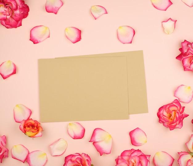 Boccioli di rosa rosa e busta di carta marrone su una superficie beige