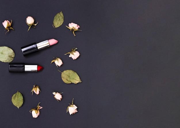 Boccioli di rosa rosa e foglie verdi con un rossetto rosso e rosa aperto su sfondo nero