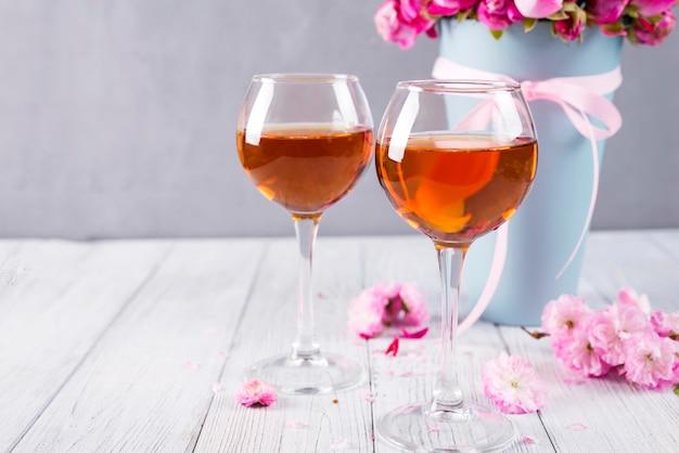 Boccioli di rose rosse e bicchieri di vino