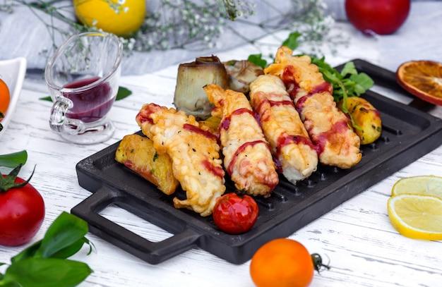 Bocconcini di pesce croccanti serviti con potaot, salsa al melograno e melanzane fritte