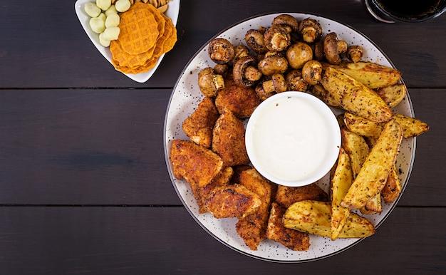Bocconcini di pollo con ketchup, patatine fritte, funghi al forno e cola
