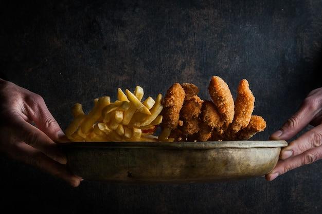 Bocconcini di pollo con patatine fritte e mano umana in piatti di argilla