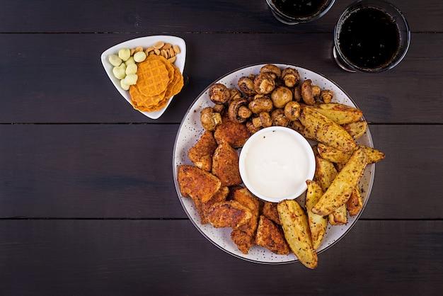 Bocconcini di pollo fast food con ketchup, patatine fritte, funghi al forno e cola.