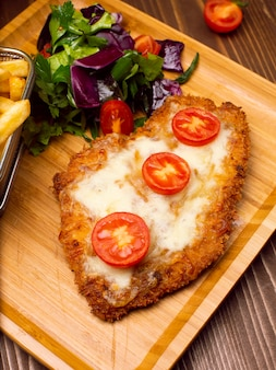 Bocconcini di pollo, patatine fritte. pepite e patate fritte con insalata e formaggio fuso.