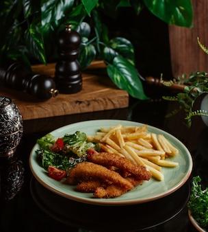 Bocconcini di pollo sottili con patatine fritte e insalata vegana.