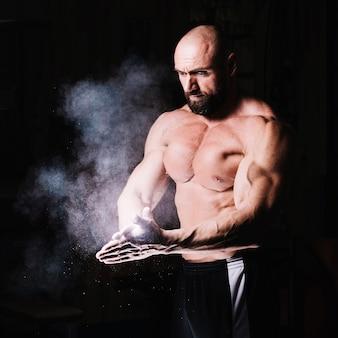 Bodybuilder battendo le mani insieme con il talco