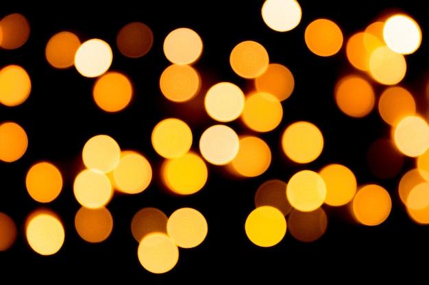 Bokeh astratto non focalizzato dell'oro su fondo nero. sfocato e sfocato molte luci rotonde