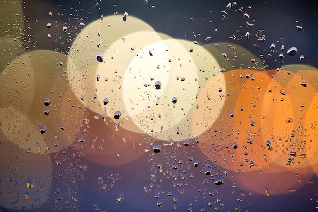Bokeh colorato astratto con cerchi gialli e gocce d'acqua sulla superficie del vetro di fronte. luci sfocate della città.