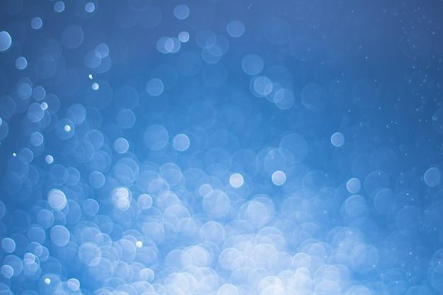 Bokeh defocused astratto delle luci come fondo dell'acqua dello spruzzo, equilibrio bianco differente