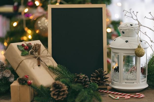 Bokeh di natale decorato con lavagna, confezione regalo, lanterna bianca, pigna, bastoncino di zucchero.