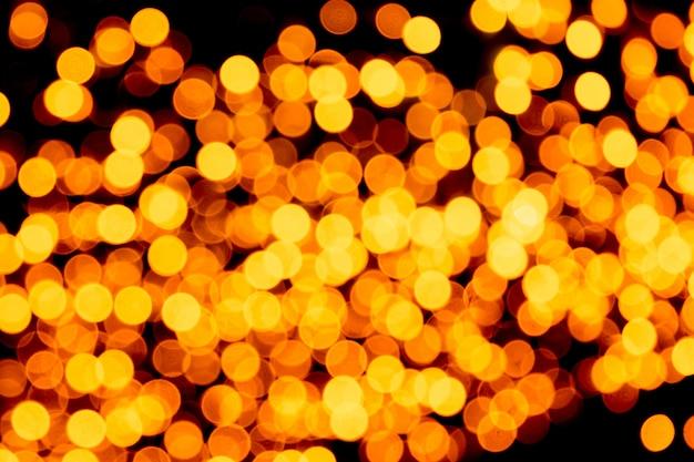 Bokeh giallo astratto non focalizzato su fondo nero. sfocato e sfocato molte luci rotonde