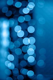Bokeh glitter delle luci notturne delle classiche ghirlande blu del 2020. sfondo verticale per creatività e design.