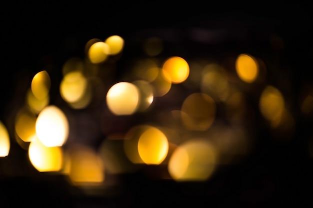 Bokeh sfocato oro su sfondo nero. bagliore d'ardore delle luci gialle nel buio, riflessioni
