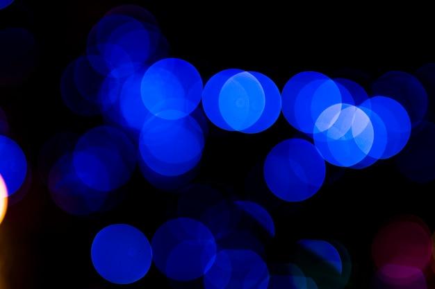 Bokeh vago luce circolare blu astratta su fondo scuro