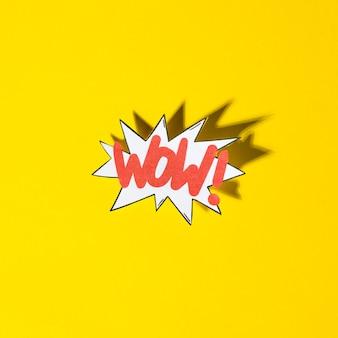 Bolla di boom comico con testo di espressione wow con ombra su sfondo giallo
