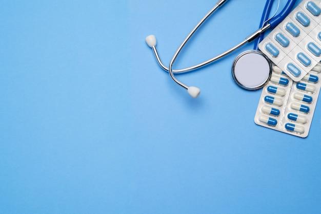 Bolla di capsule capsule e stetoscopio isolato su sfondo blu