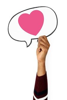 Bolla di discorso della holding della mano con l'icona del cuore