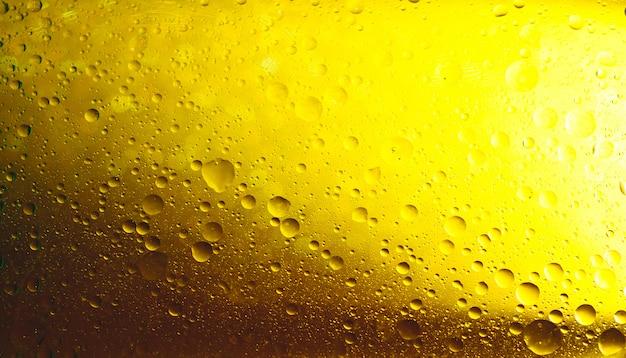 Bolle d'acqua disposte uniformemente in uno sfondo giallo astratto.