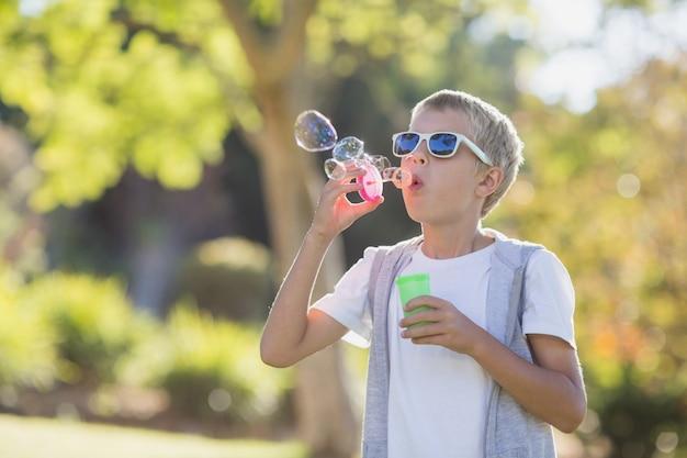 Bolle di salto del giovane ragazzo attraverso la bacchetta della bolla