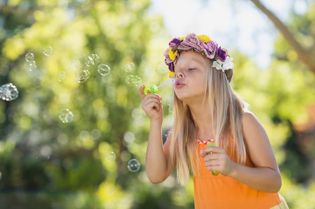 Bolle di salto della ragazza attraverso la bacchetta della bolla