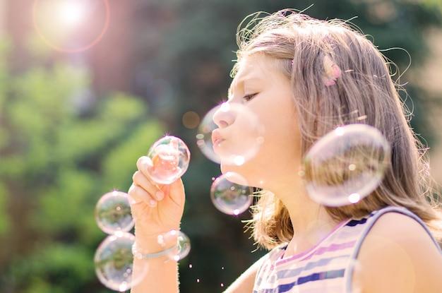 Bolle di sapone di salto della bambina nel parco