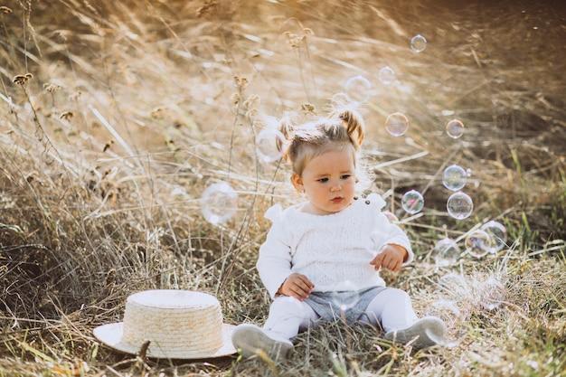 Bolle di sapone di salto della piccola neonata nel campo