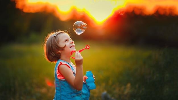 Bolle di sapone di salto della ragazza caucasica caucasica di cinque anni all'aperto al tramonto.