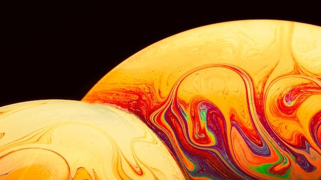 Bolle di sapone saturate artistiche di pendenza su fondo nero