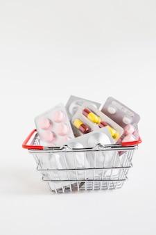 Bolle differenti della medicina nel canestro dell'acciaio inossidabile su fondo bianco